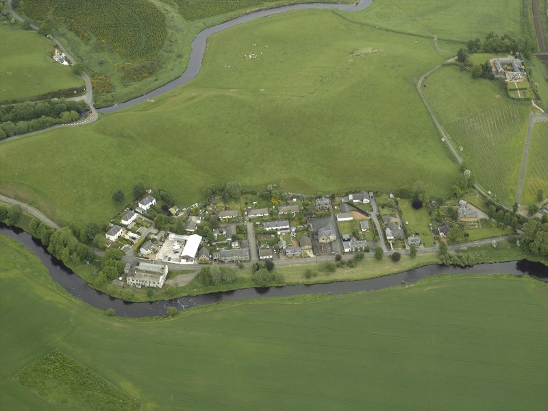Oblique aerial view of the village centred on the woollen mill, taken from the WSW.