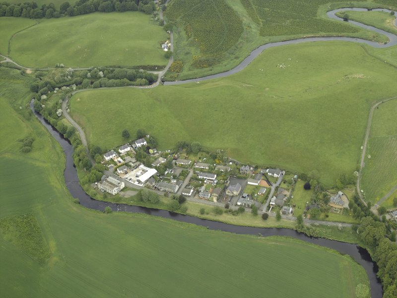 Oblique aerial view of the village centred on the woollen mill, taken from the SSW.