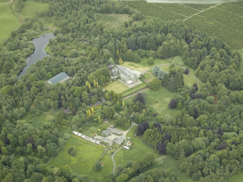 Oblique aerial view centred on the country house, walled garden and farmsteading, taken from the SSW.