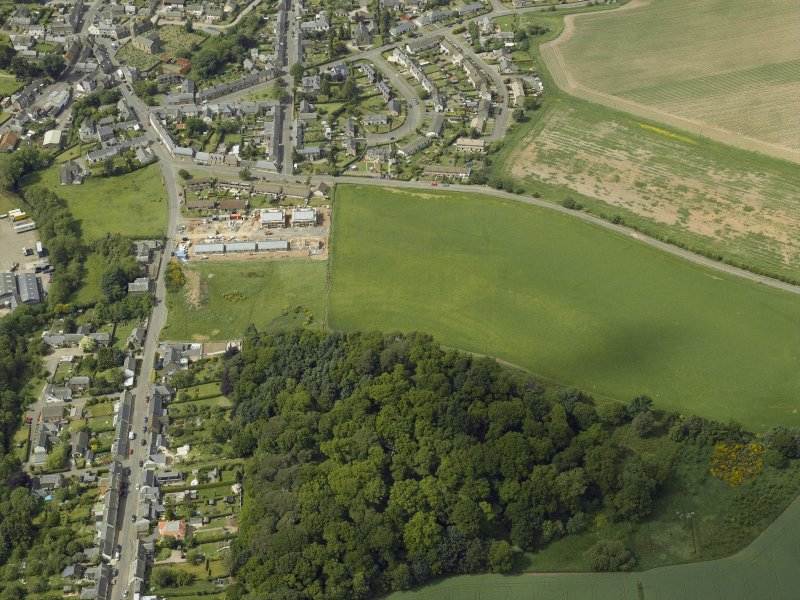 Oblique aerial view centred on the cropmarks of the fort with the village, church and burial-ground adjacent, taken from the SE.