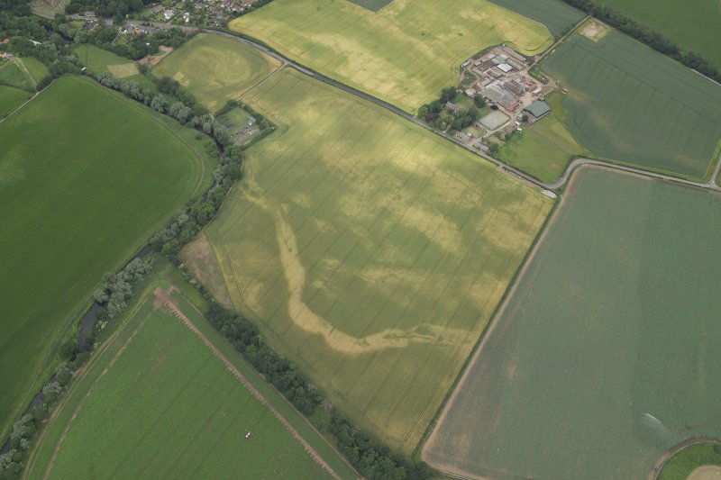 Oblique aerial view centred on the cropmarks of the cursus with the cropmarks of the possible settlement and the farmhouse, farm buildings and dovecot adjacent, taken from the SE.