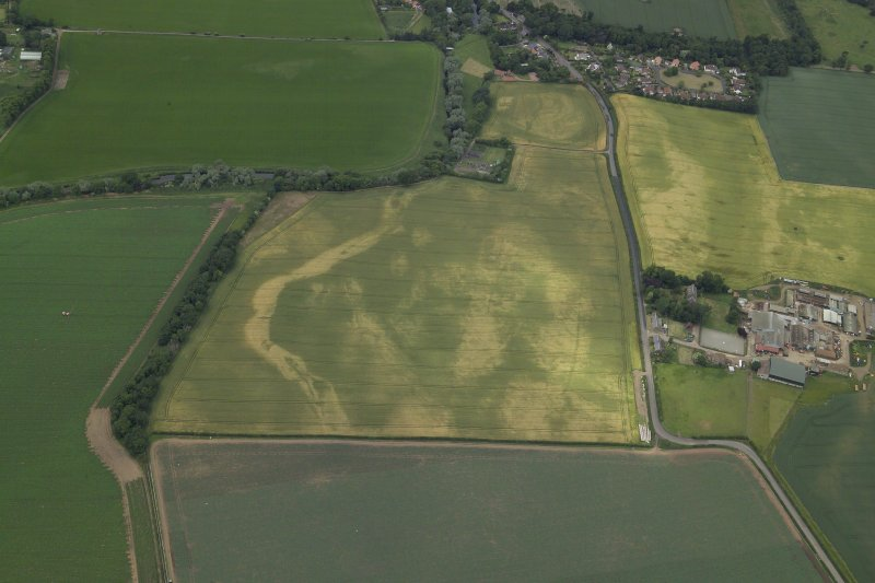 Oblique aerial view centred on the cropmarks of the cursus with the cropmarks of the possible settlement and the farmhouse, farm buildings and dovecot adjacent, taken from the ENE.