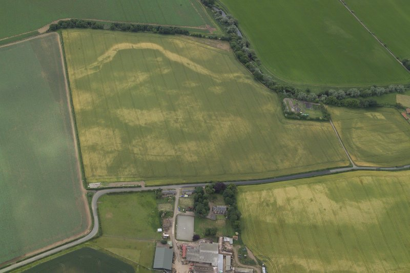 Oblique aerial view centred on the cropmarks of the cursus with the cropmarks of the possible settlement and the farmhouse, farm buildings and dovecot adjacent, taken from the NNW.