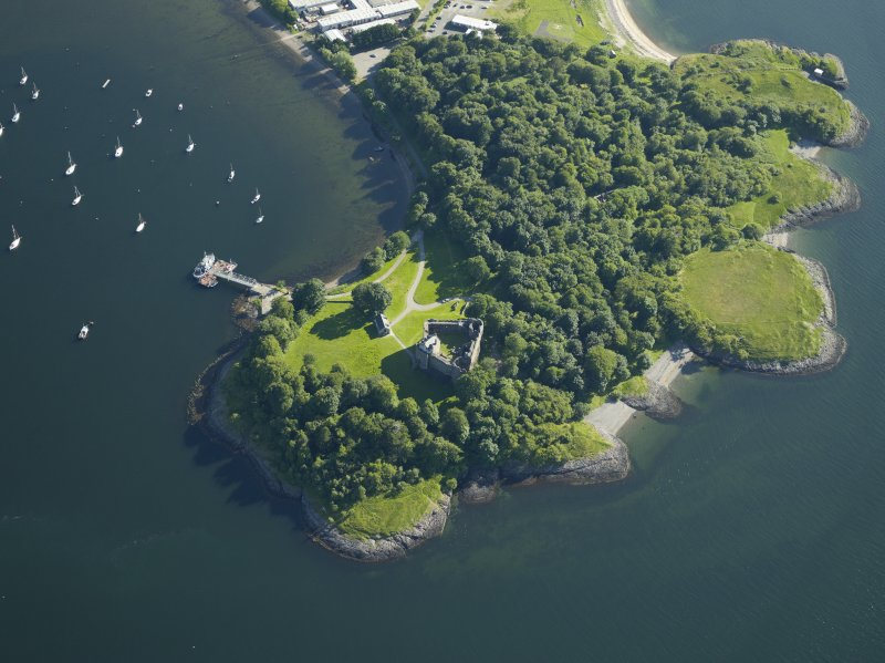 Oblique aerial view centred on the remains of the castle with the pier adjacent, taken from the NE.