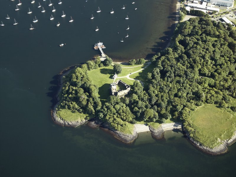 Oblique aerial view centred on the remains of the castle with the pier adjacent, taken from the N.