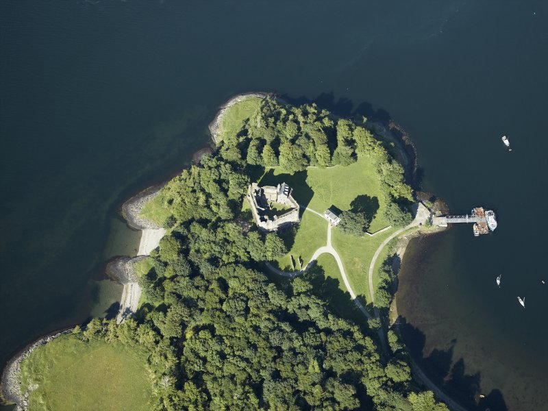 Oblique aerial view centred on the remains of the castle with the pier adjacent, taken from the WSW.