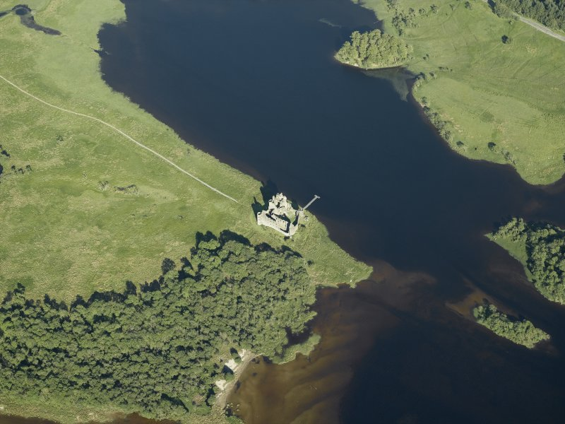 Oblique aerial view centred on the remains of the castle, taken from the WNW.