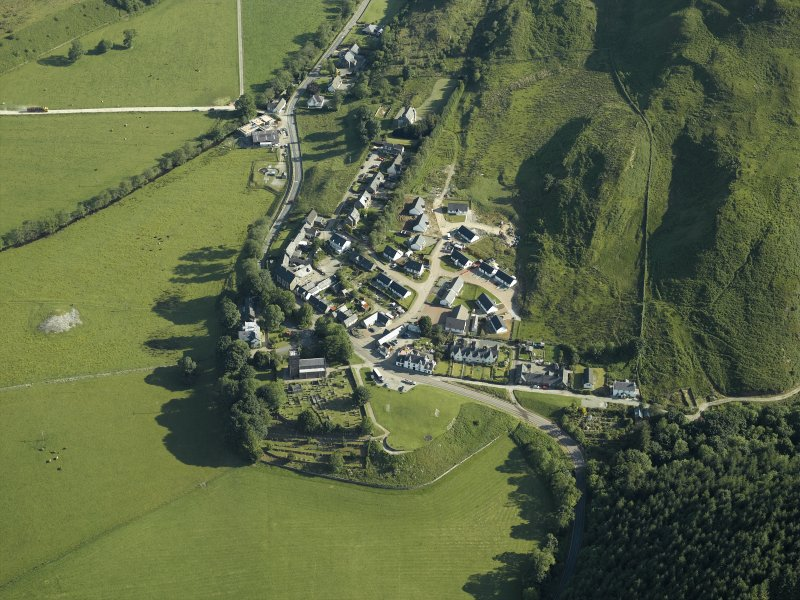 General oblique aerial view of the village, centred on the church, churchyard, burial ground, museum and the remains of the cairn with the tower-house adjacent, taken from the SSW.
