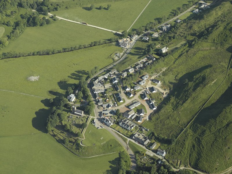 General oblique aerial view of the village, centred on the church, churchyard, burial ground, museum and the remains of the cairn with the tower-house adjacent, taken from the SE.