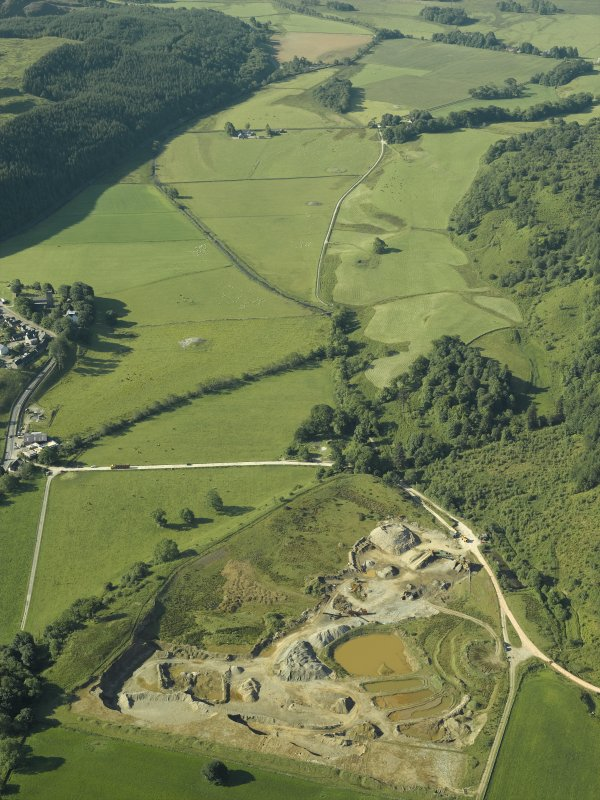 General oblique aerial view centred on the gravel quarry and the site of the excavation of the pit-defined enclosure with the church, churchyard, burial-ground, museum and remains of the cairns adjacent, taken from the NNE.