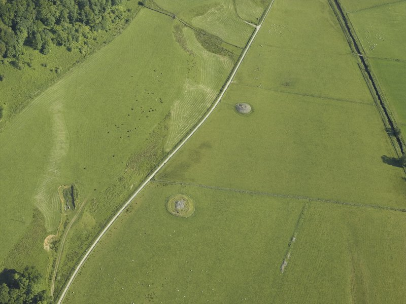 Oblique aerial view centred on the remains of the cairns, taken from the SSE.