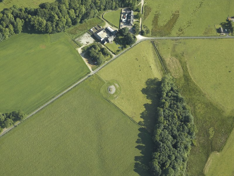 Oblique aerial view centred on the remains of the chambered cairn with the remains of the standing stone and the school and farmstead adjacent, taken from the S.