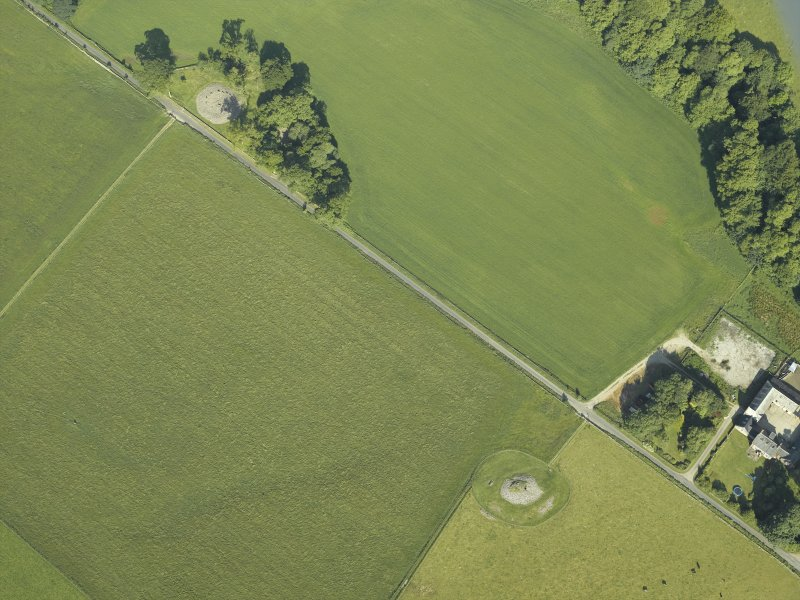 Oblique aerial view centred on the remains of the chambered cairn with the remains of the standing stone and stone circles and the farmstead adjacent, taken from the ESE.