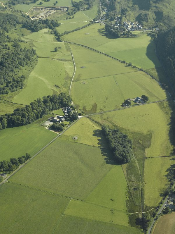 General oblique aerial view of the Kilmartin valley centred on the remains of the chambered cairn, standing stones, stone setting and cairns and the farmstead and school, taken from the S.