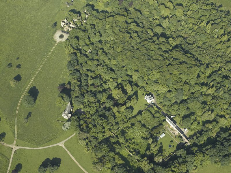 General oblique aerial view centred on the ruins of the country house with the church and walled garden adjacent, taken from the NNE.