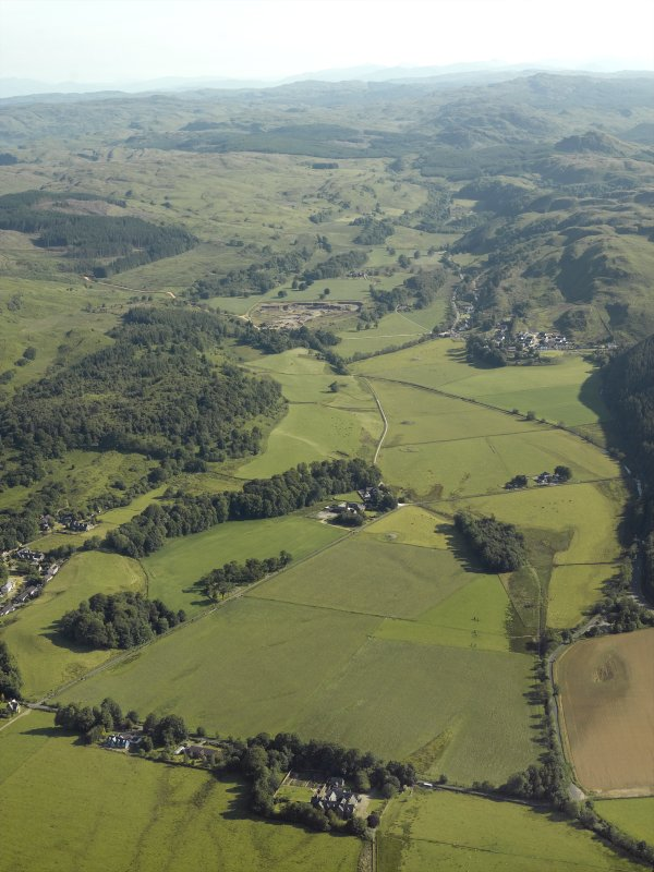 General oblique aerial view of the Kilmartin valley centred on the remains of the chambered cairn, standing stones, stone setting and cairns and the farmstead and school, taken from the SSW.