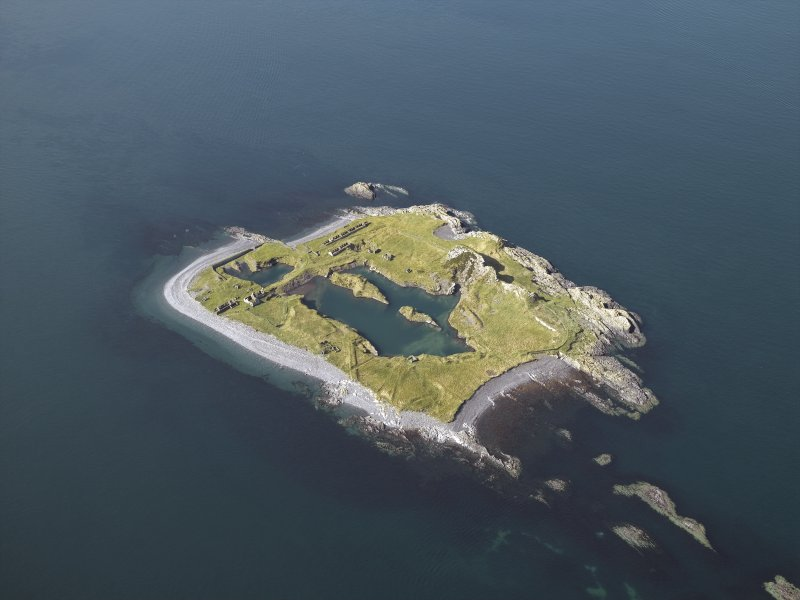 Oblique aerial view of the island, centred on the remains of the slate quarries, taken from the NE.