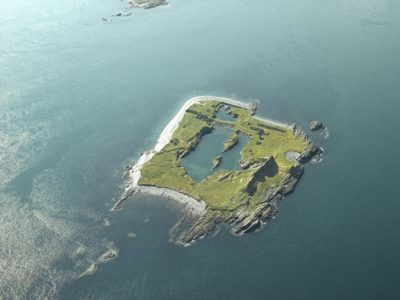 Oblique aerial view of the island, centred on the remains of the slate quarries, taken from the NW.