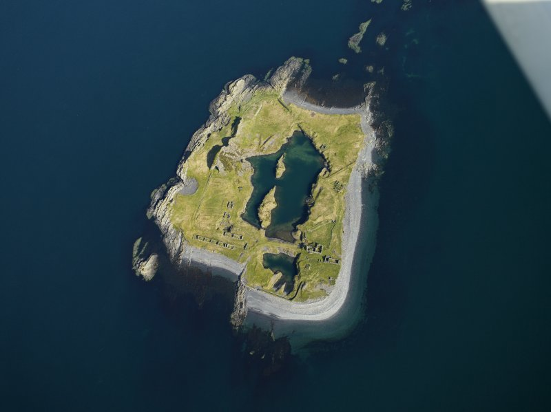 Oblique aerial view of the island, centred on the remains of the slate quarries, taken from the SE.