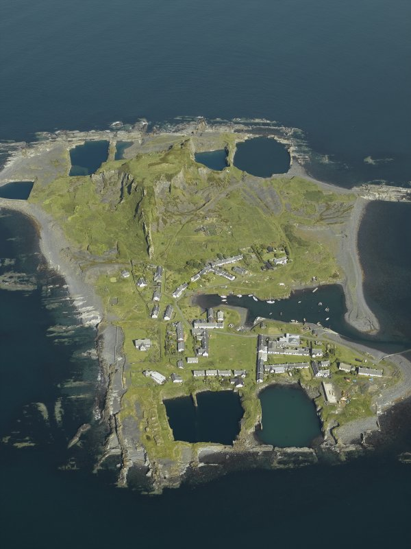 Oblique aerial view of the island, centred on the remains of the quarries and the harbour, taken from the SE.