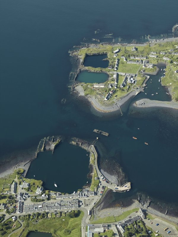 General oblique aerial view centred on the village and the remains of the slate quarries with the slate quarry and harbour adjacent, taken from the NE.