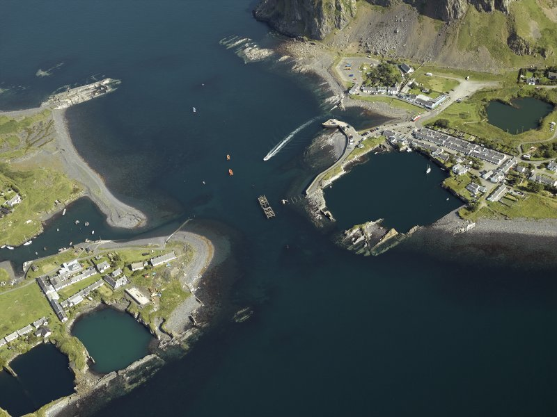 General oblique aerial view centred on the village and the remains of the slate quarries with the slate quarry and harbour adjacent, taken from the S.