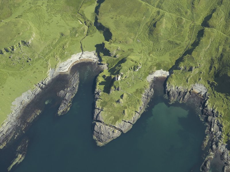 Oblique aerial view centred on the remains of Gylen Castle, Kerrera, and farmstead and the entrance to the cave, taken from the S.