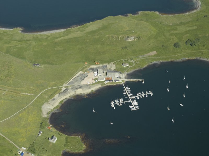 Oblique aerial view centred on the remains of the seaplane base and the boatyard with the house adjacent, taken from the SE.