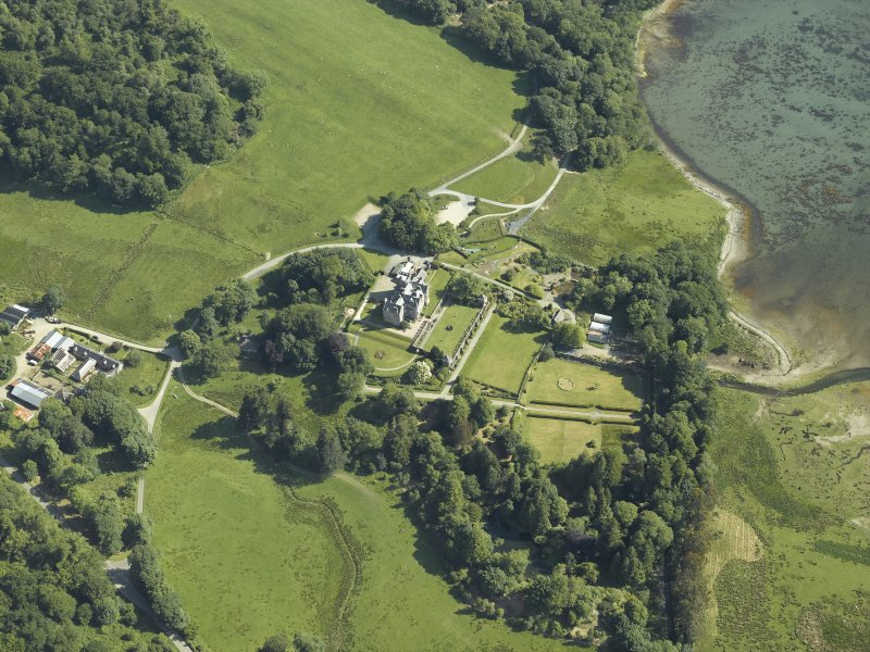 Oblique aerial view centred on the country house, terraced garden and dovecots with the farmsteading, farmhouse and stables adjacent, taken from the SW.