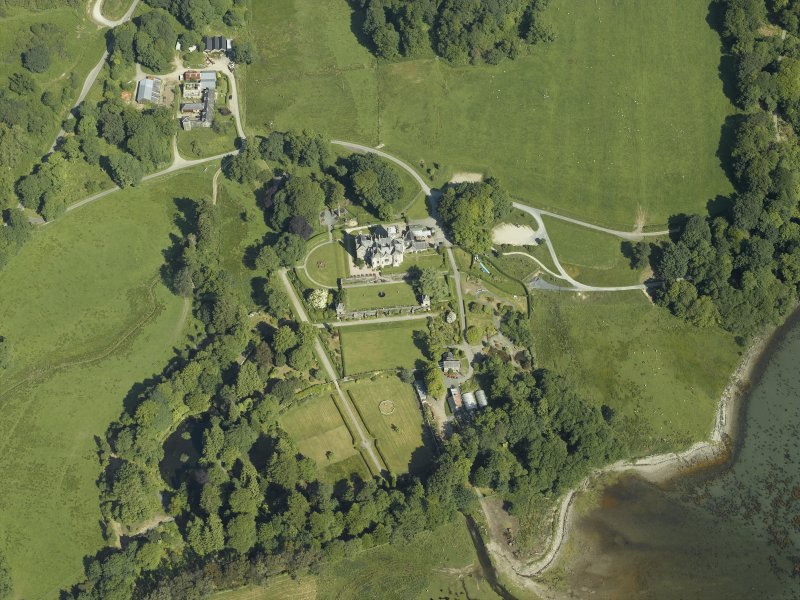 Oblique aerial view centred on the country house, terraced garden and dovecots with the farmsteading, farmhouse and stables adjacent, taken from the SE.