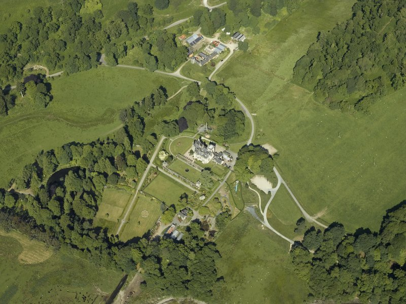 Oblique aerial view centred on the country house, terraced garden and dovecots with the farmsteading, farmhouse and stables adjacent, taken from the ESE.