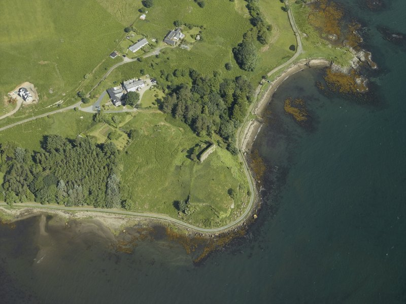 Oblique aerial view centred on the remains of the castle, hall-house and building with the farmhouse and farmsteading adjacent, taken from the S.