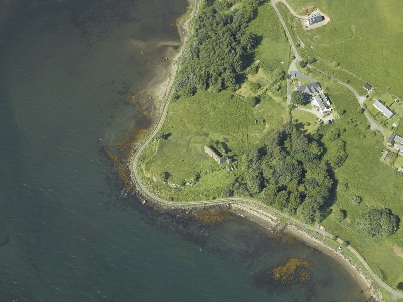 Oblique aerial view centred on the remains of the castle, hall-house and building with the farmhouse and farmsteading adjacent, taken from the NE.