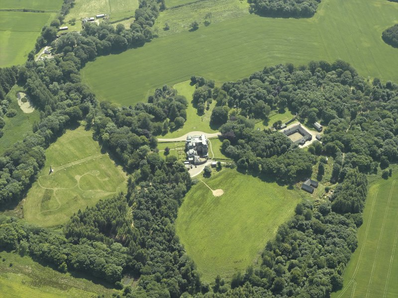 Oblique aerial view centred on the country house, stable block and walled garden, taken from the N.