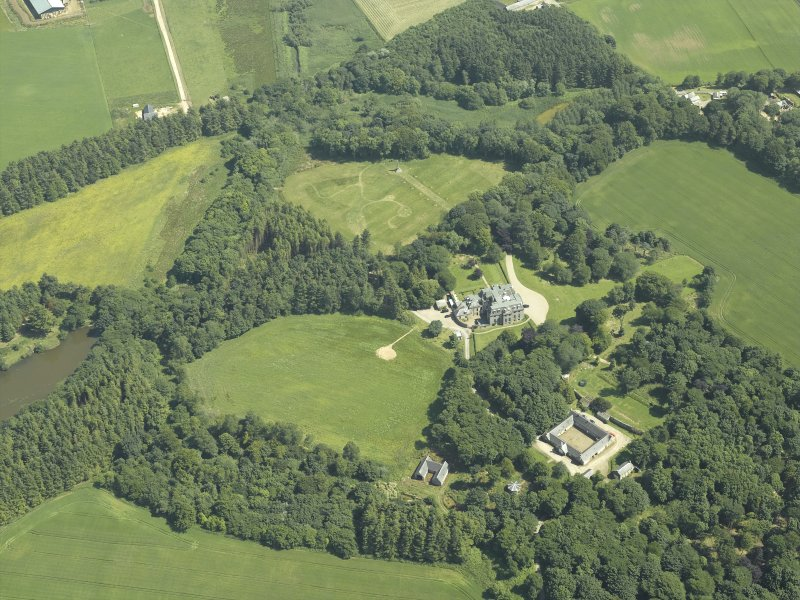 Oblique aerial view centred on the country house, stable block and walled garden, taken from the NW.