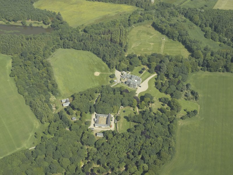Oblique aerial view centred on the country house, stable block and walled garden, taken from the WSW.