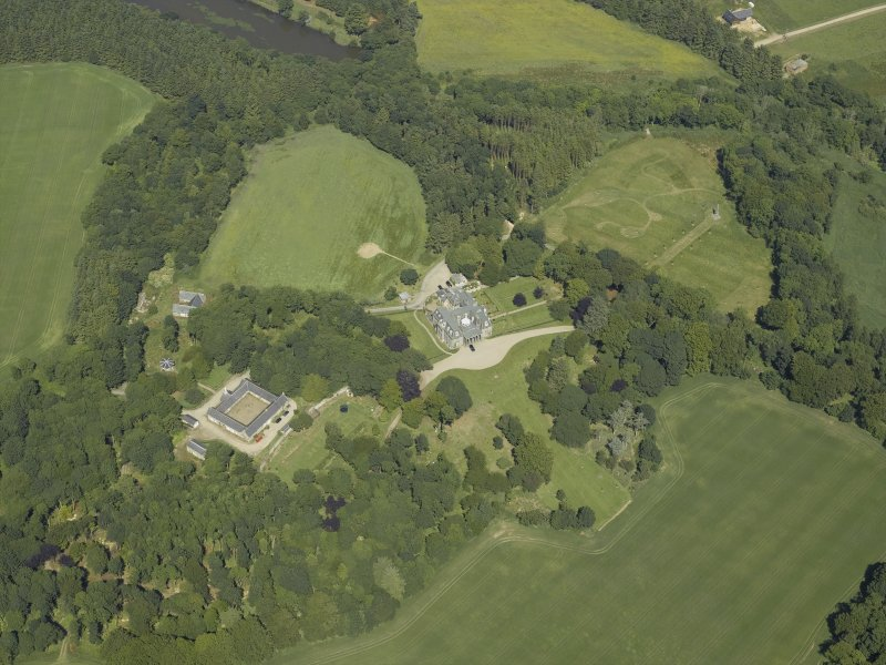 Oblique aerial view centred on the country house, stable block and walled garden, taken from the SSW.