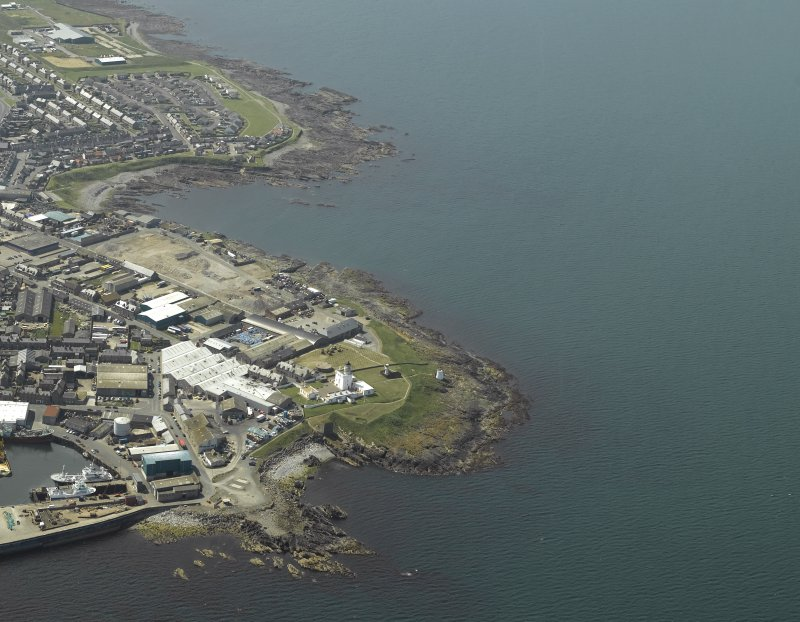 Oblique aerial view centred on the lighthouse and museum with the remains of the tower adjacent, taken from the E.