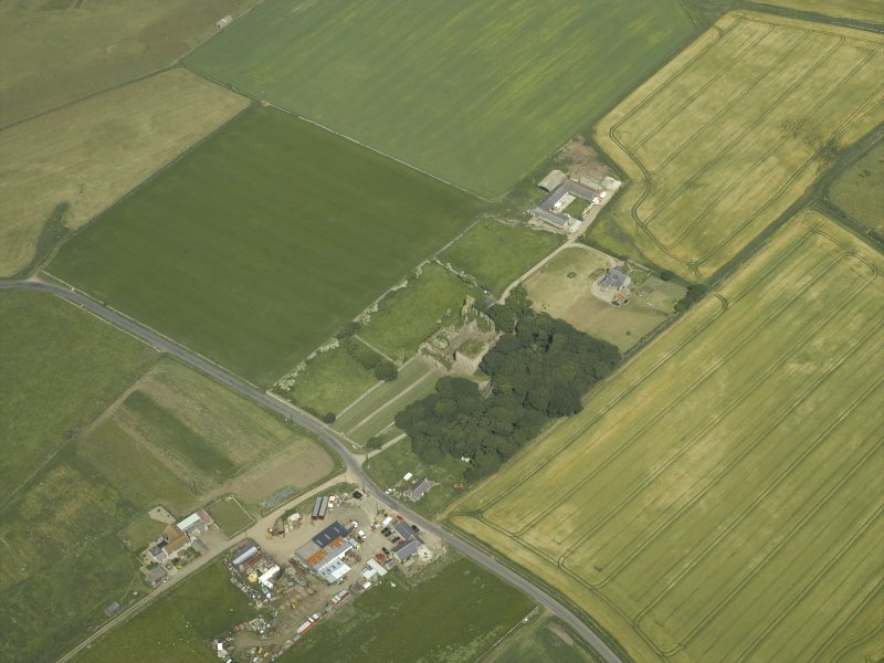 Oblique aerial view centred on the remains of the castle and tower-house, taken from the SW.