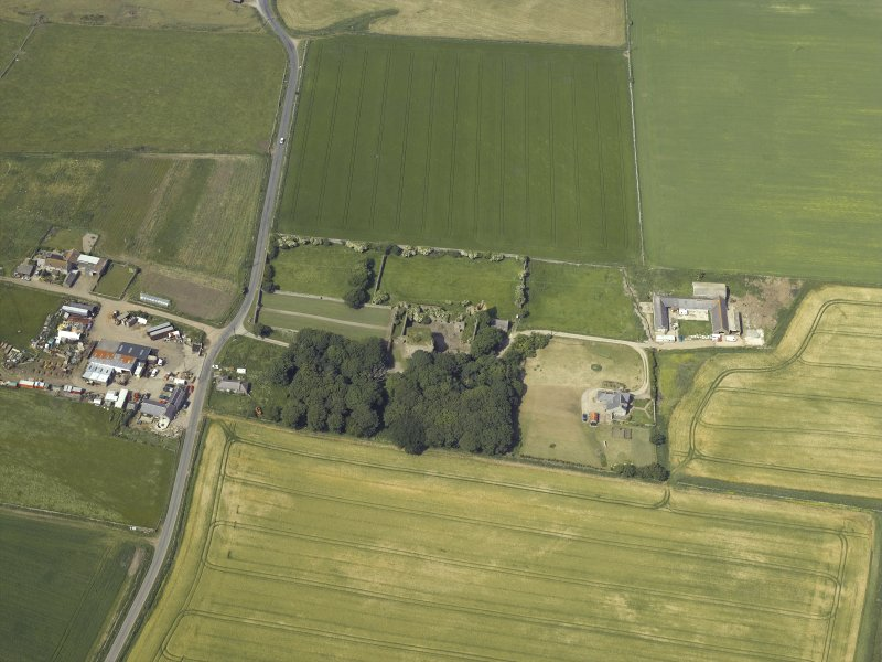 Oblique aerial view centred on the remains of the castle and tower-house, taken from the SSE.