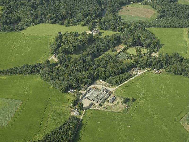 General oblique aerial view centred on the castle, tower-house, walled garden and farmsteading, taken from the S.