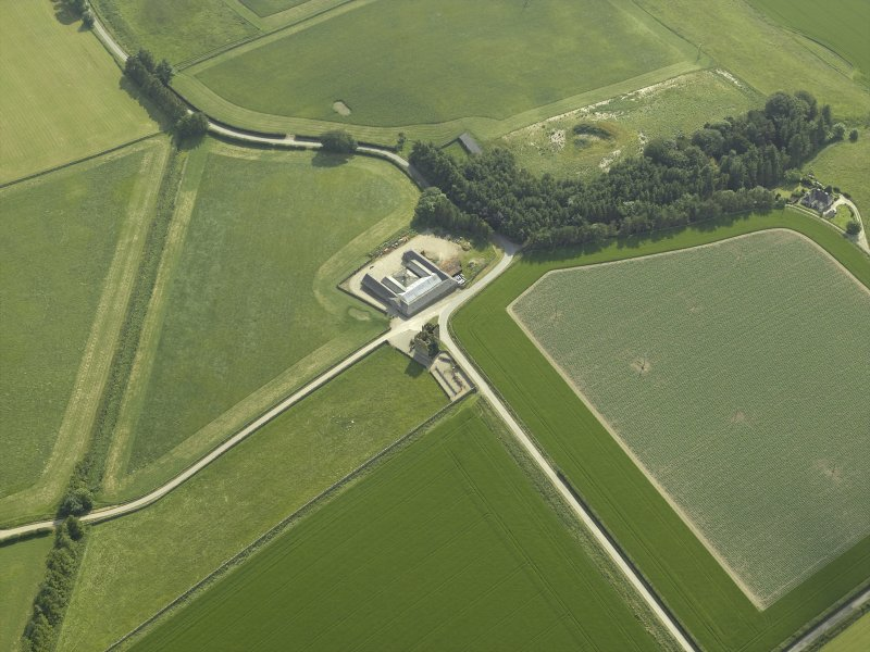 Oblique aerial view centred on the remains of the castle and the farmsteading, taken from the NE.