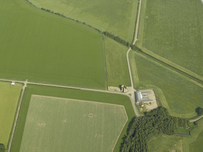 Oblique aerial view centred on the remains of the castle and the farmsteading, taken from the WNW.