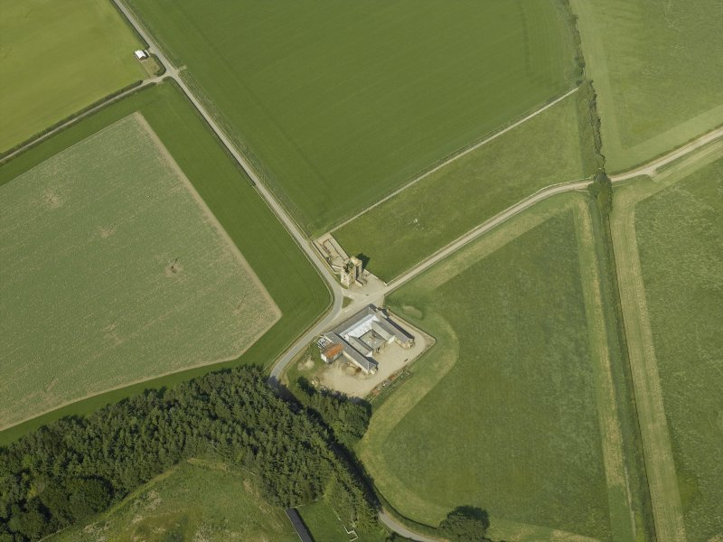 Oblique aerial view centred on the remains of the castle and the farmsteading, taken from the SW.