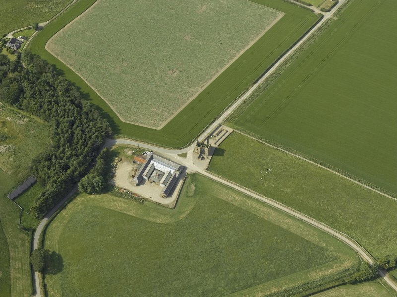 Oblique aerial view centred on the remains of the castle and the farmsteading, taken from the SSE.