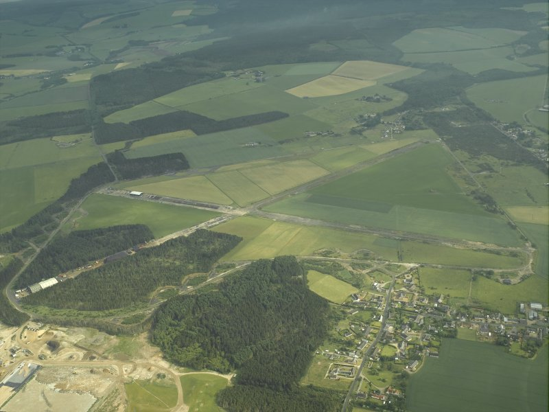 General oblique aerial view centred on the remains of the airfield with the village adjacent, taken from the NNW.