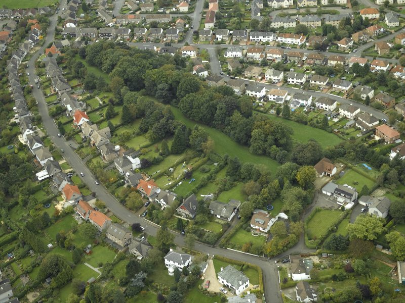 Oblique aerial view centred on the course of the Antonine Wall with the housing adjacent, taken from the SE.