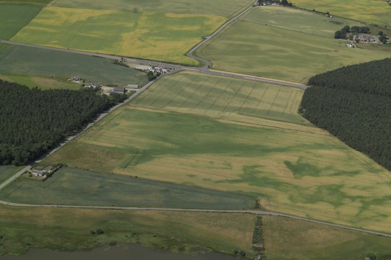 General oblique aerial view centred on the cropmarks of the roundhouses, pits and possible souterrain with the cropmarks of the ring-ditch and the farmsteading adjacent, taken from the SE.