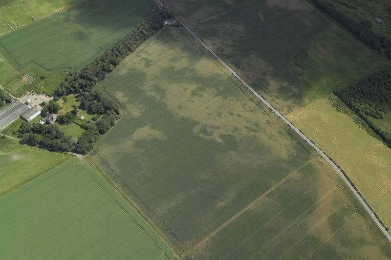 Oblique aerial view centred on the cropmarks of the possible enclosure and the pits, taken from the WNW.