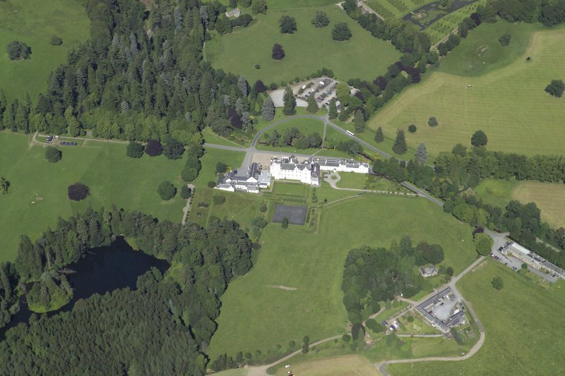 General oblique aerial view centred on the country house, bridge and gardens with the dairy, offices and church adjacent, taken from the SW.